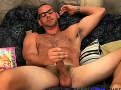 Hot bear to glasses plays with his weasel words while leafing through a gay porn mag