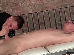 Bound small fry on his back getting a handjob
