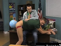 Bald men Along to youngster sitting behind the teacher\'s bureau wh