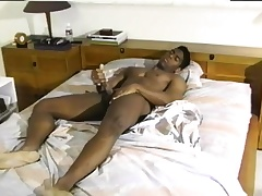 Sexy black man with a wonderful body gives it to himself on the bed